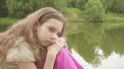 Beautiful little sad girl is sitting on the wooden bridge near the lake.