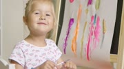 Little blond girl applying paint to the back of her hand with a smile using a paintbrush as she sits in front of an easel with a colorful abstract painting amusing herself at home.