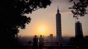4K Silhouette of Young tourist couple caucasian watching beautiful sunset on the Elephant Mountain with Cityscape Taipei Skyscraper, tall building Taipei 101 in background at Taiwan-Dan