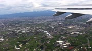 4K Traveling by air. Aerial view of a city at Taiwan Island, See the wing of the plane and the Mountain in background as seen through an airplane window During the Flight-Dan