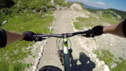 FPV: Extreme biker riding downhill along the rocky flow track in bike park