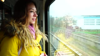 Portrait of cute girl who watches over view from window on train and looks forward to getting off transport at station. European-looking girl with long blond hair smiles and looks at camera, and